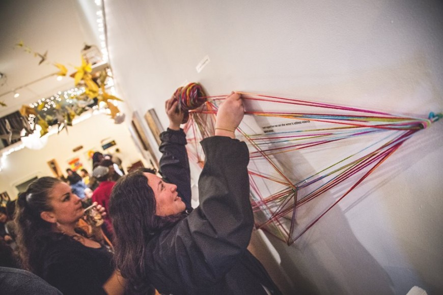 """An interactive part of the """"When She Rises"""" exhibit, collaboratively created by Vanessa Camarena, Cece Carpio and Erin Yoshi, invites visitors to loop rainbow-hued yarn around nails marked by text describing experiences of harassment, abuse and violence they had encountered."""